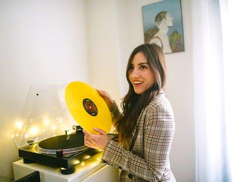 黄色のビニールレコードを保持している女性