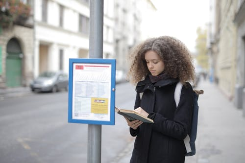 Woman in Black Coat Holding Book