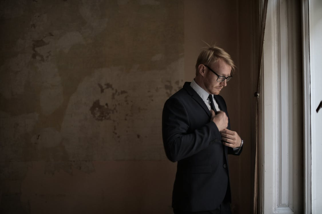 Pensive man in suit and eyeglasses standing near window in shabby hallway