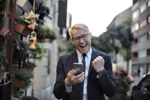 Excited young man in formal wear and eyeglasses clenching fist and rejoicing victory while using mobile phone in modern city street