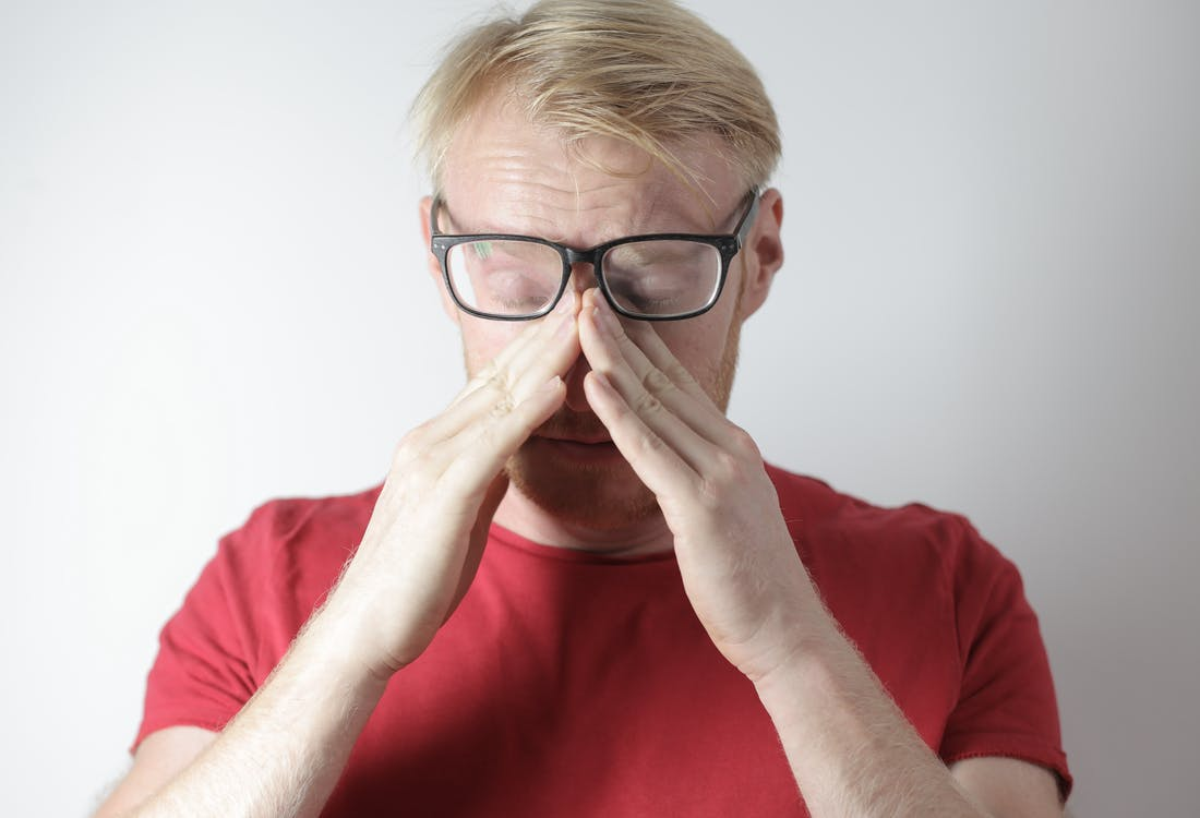 Exhausted mature man rubbing nose bridge after wearing glasses near gray wall