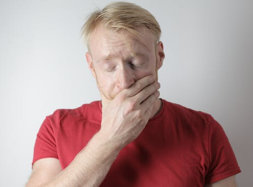 Mature man in red t shirt being in shock after getting news standing with closed eyes near gray wall in room