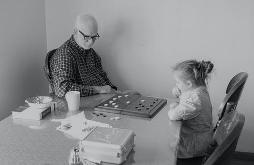 Man And Little Girl Playing Checkers