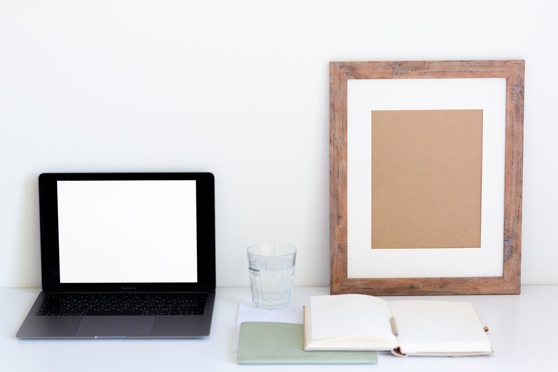 Laptop with blank screen and glass of water placed on white desk near empty frame and blank notepad against white wall