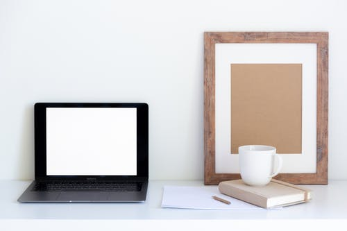 Minimalistic workplace with laptop and empty frame with office attributes during coffee break