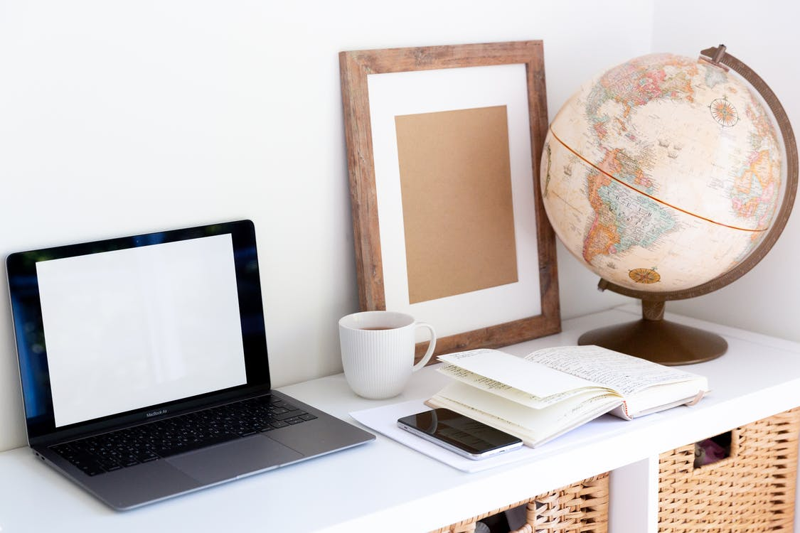 Laptop with empty screen placed near smartphone and organizer with blank frame and retro glove aside during coffee break in room