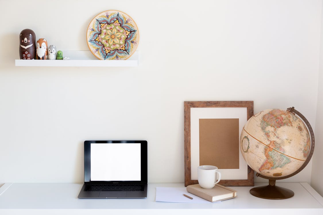 Interior of cozy home office with netbook frame globe organizer and vintage decor elements