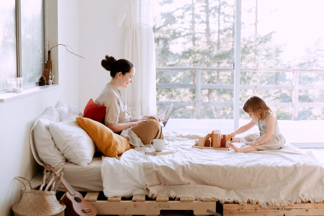 Full body of happy mother surfing netbook and daughter playing with toys on bed against window