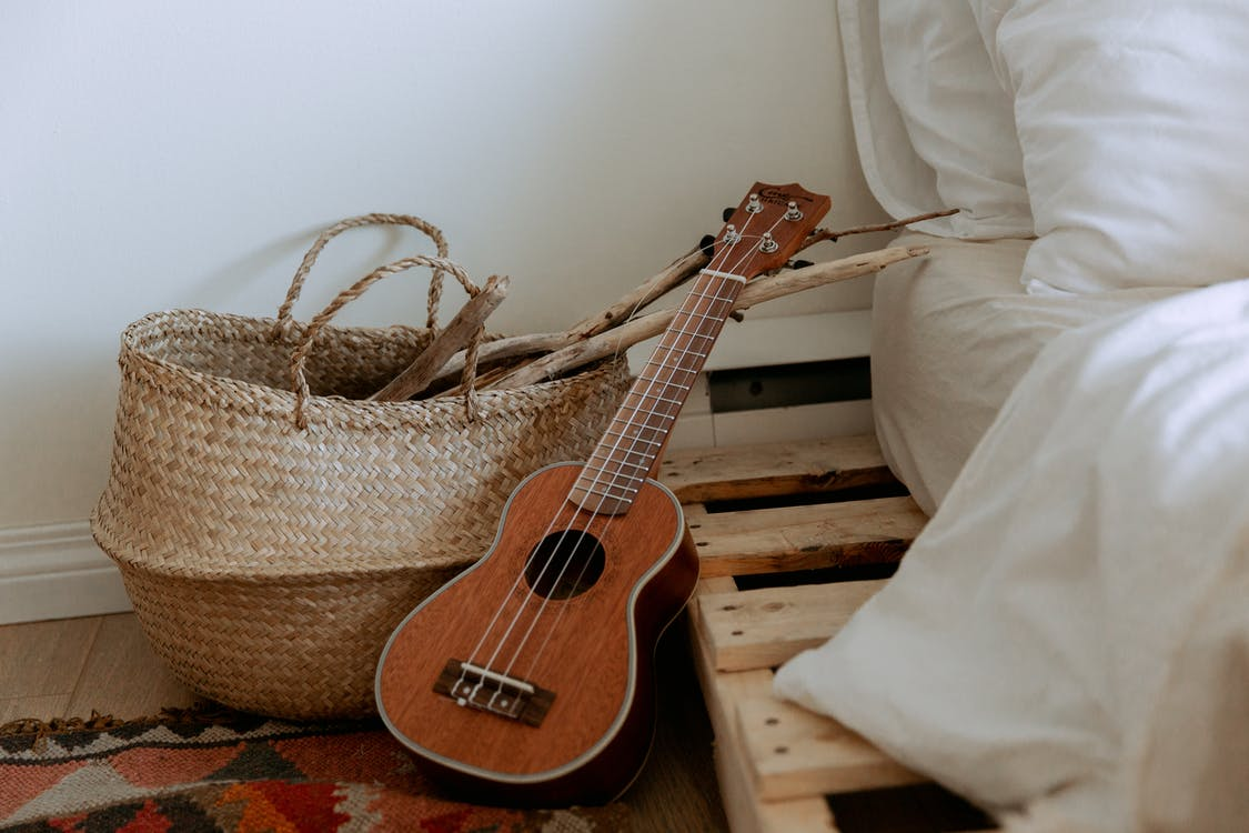 Interior with wooden branches in wicker basket and small guitar near bed