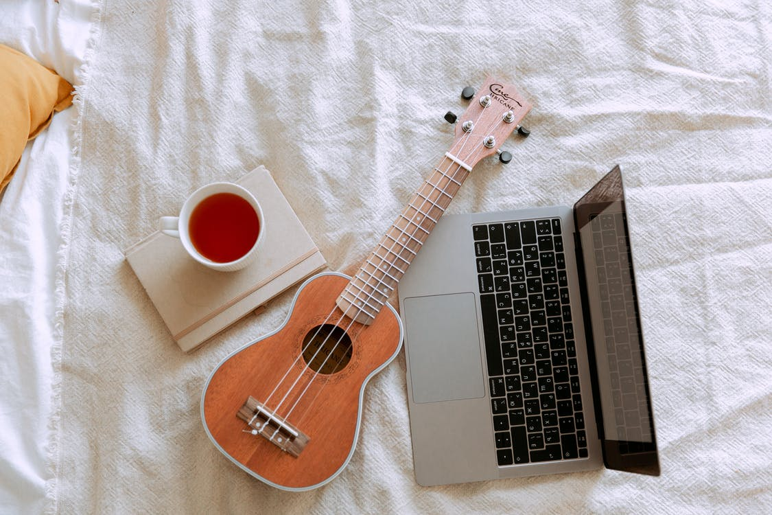 Top view of morning learning ukulele play process in bed