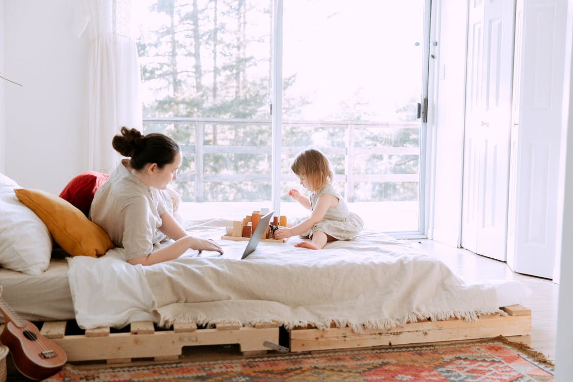 Young woman using laptop in bed while daughter playing on sunny morning