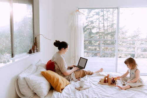Side view of cute toddler girl sitting on bed barefoot and playing with colorful wooden blocks while mother using laptop in bed enjoying morning coffee