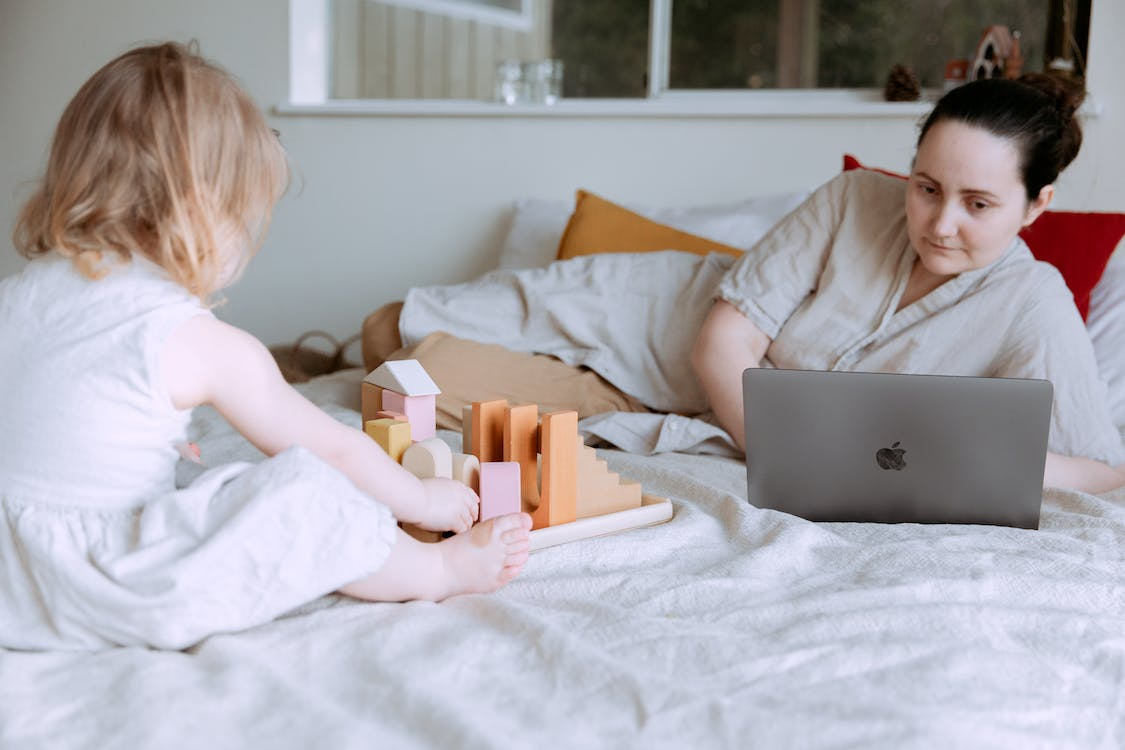 Cute toddler girl playing with wooden blocks on bed while mother using laptop nearby