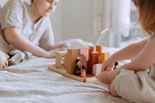 Faceless toddler girl sitting on bed and playing with wooden blocks and toys while mother using laptop