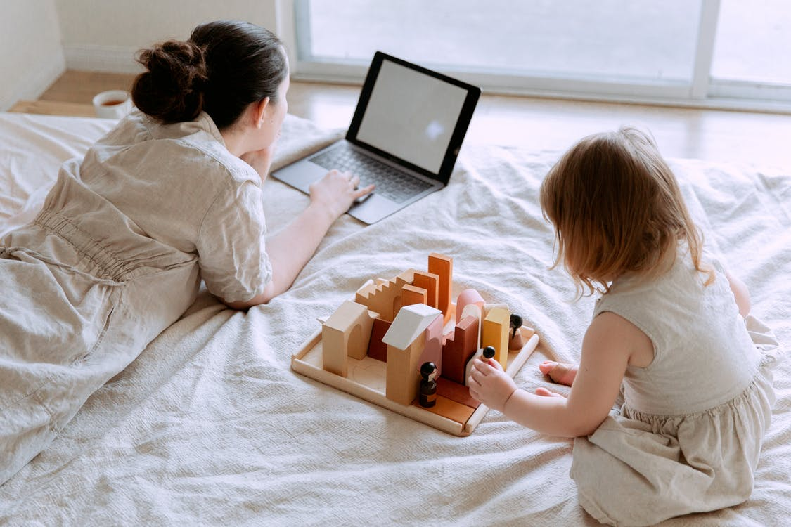 From above of young female in casual clothes lying on bed and using laptop while daughter sitting on bed and playing with wooden blocks and toys on sunny morning