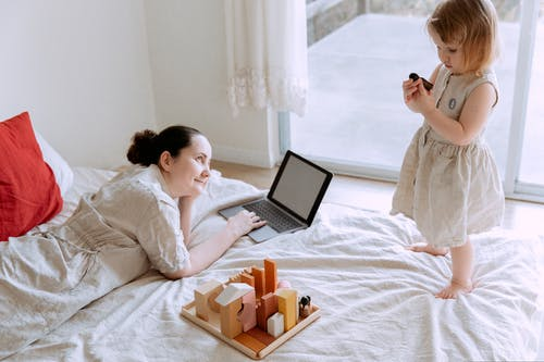 Smiling woman lying on bed with laptop and admiring daughter standing on bed barefoot