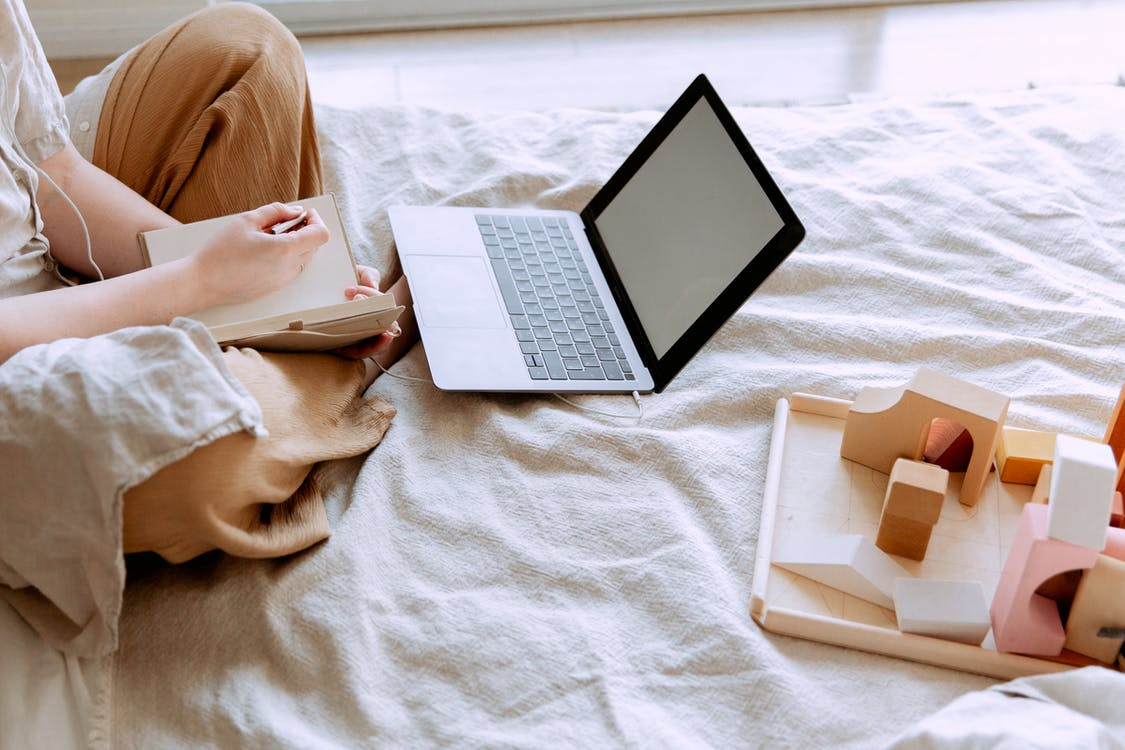 Crop woman using laptop on bed