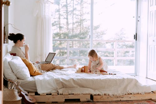 Woman using laptop while daughter playing with constructor