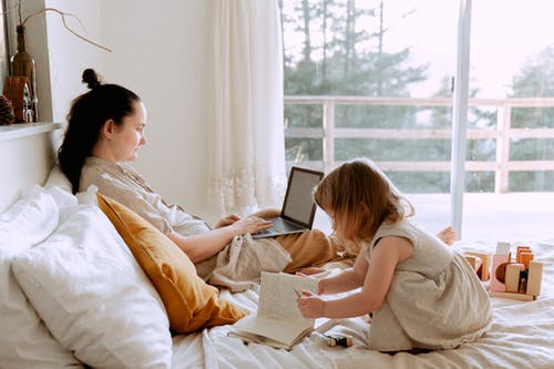Mother working remotely while daughter drawing nearby