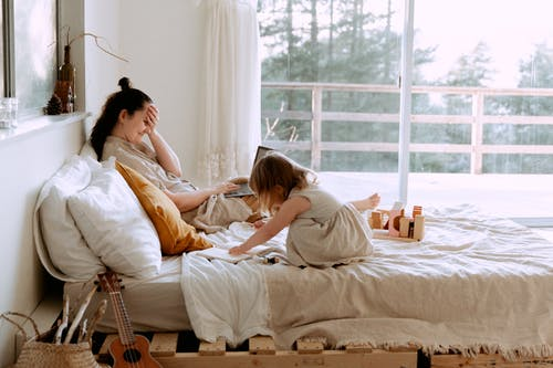 Laughing mother working and playing with daughter on bed at home