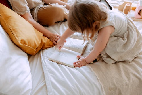 Girl drawing in notebook in bed