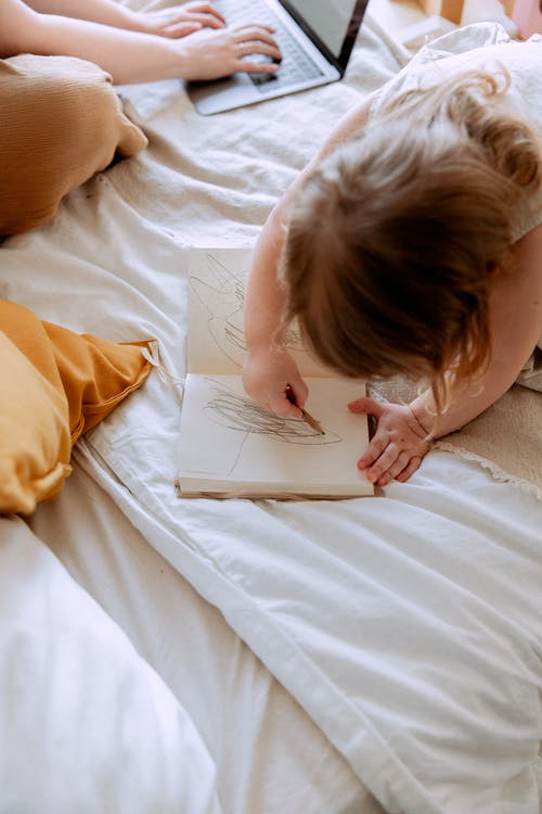 Girl drawing in notebook while mother working remotely nearby