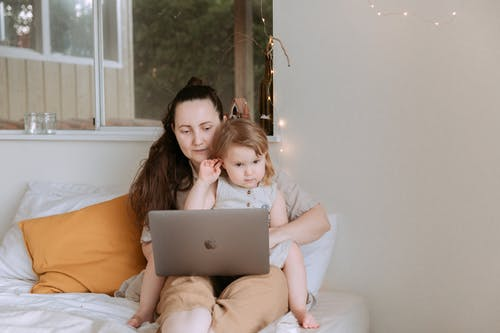 Mother showing pictures to daughter on laptop