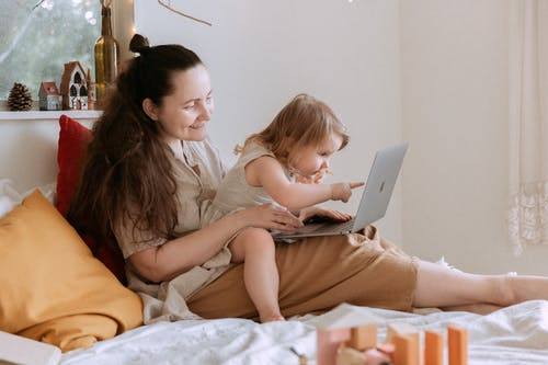 Happy mother with small daughter using laptop