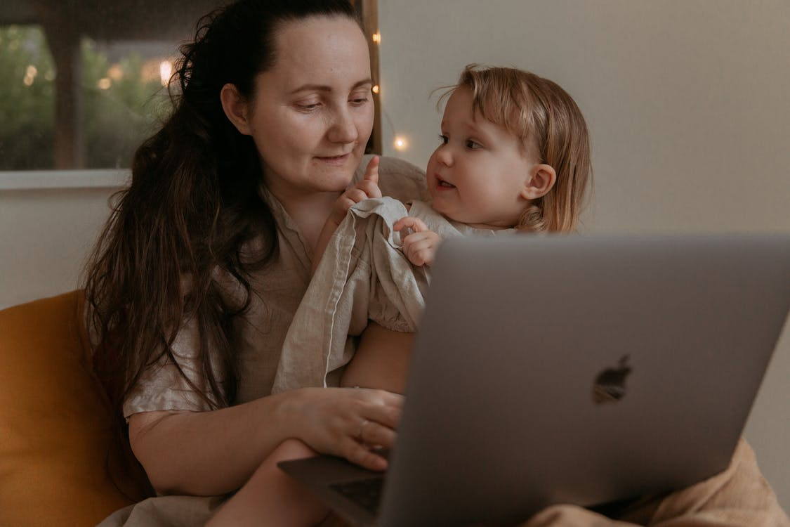 Woman trying to relax small kid while using laptop