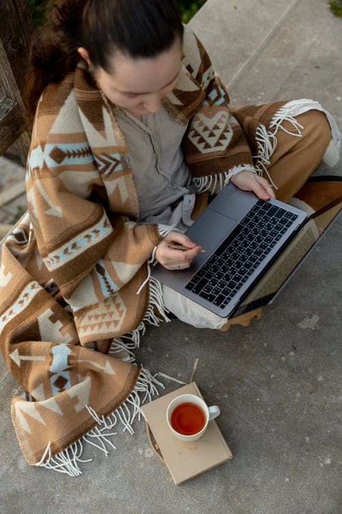 Crop freelancer in blanket surfing internet on laptop outdoors
