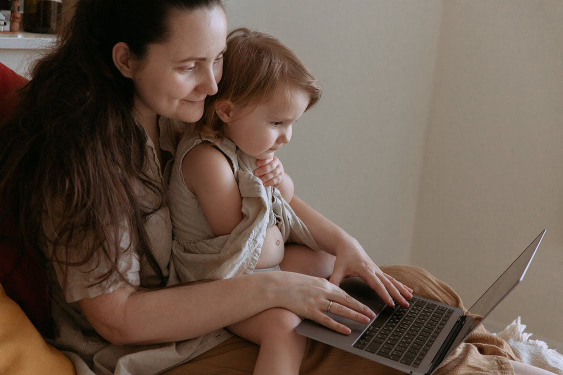 Crop mother with little daughter using social media on laptop