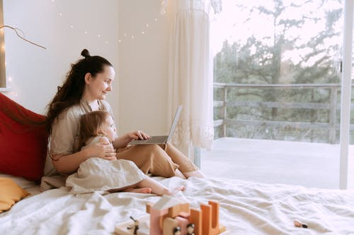 Cheerful mother cuddling daughter while sitting on bed with laptop
