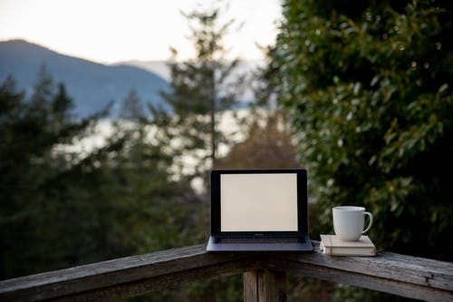 Laptop with blank screen and cup of hot drink