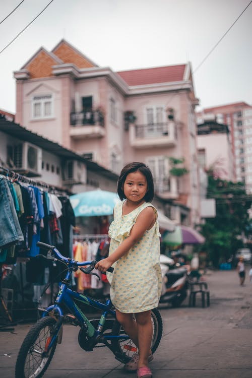 Little Girl Holding A Bike