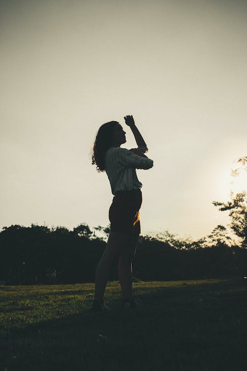 Silhouette Of Woman Standing On Grass