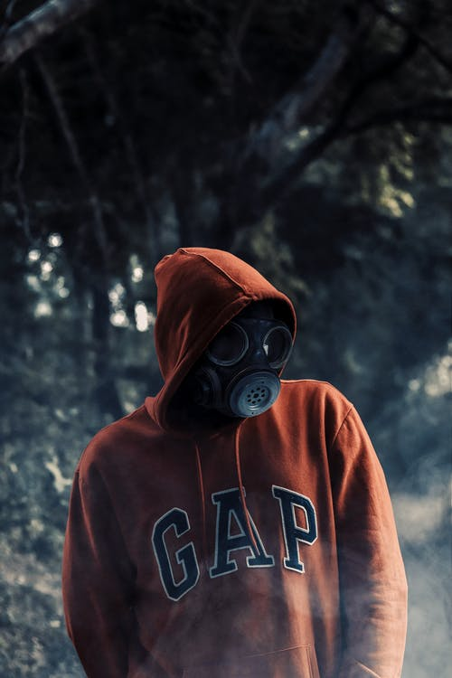 Person in Orange Hoodie Wearing Gas Mask