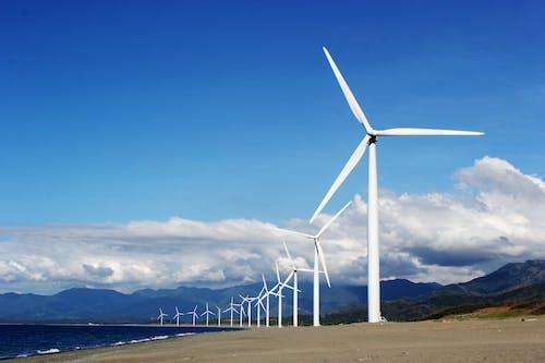 Turbinas De Viento Blanco Sobre Arena Gris Cerca Del Cuerpo De Agua