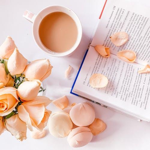 White Ceramic Mug Beside A Book