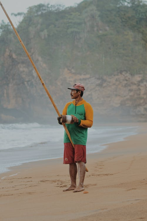 Man Standing On Shore Holding A Stick