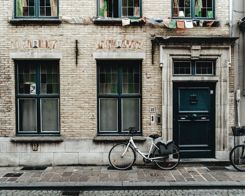 Black Bicycle Parked Beside Brown Brick Building