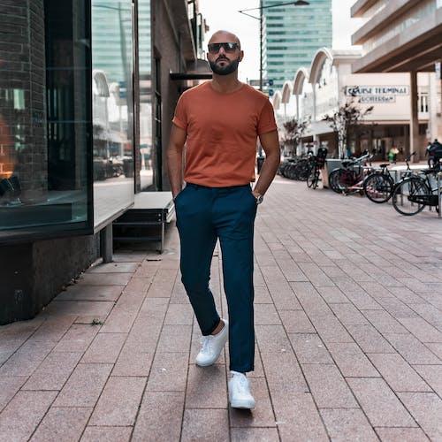 Man in Orange Tank Top Walking on Pavement