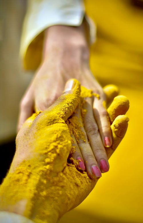 Person's Hand Covered With Yellow Powder