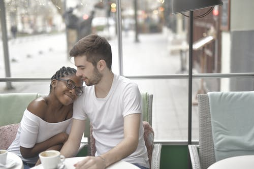 Content African American young woman in casual wear putting head to boyfriends shoulder and looking at camera while sitting in cafeteria and drinking coffee in daylight