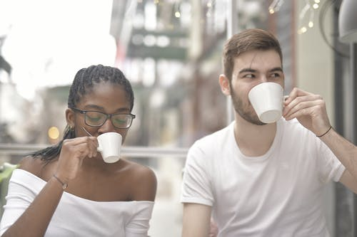 Man and Woman Drinking from White Ceramic Mug