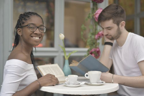 Couple Reading Books while Having Coffee