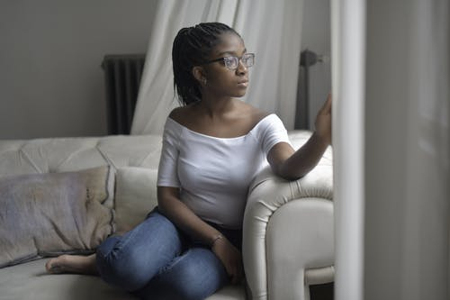 Woman in White Scoop Neck Shirt and Blue Denim Jeans Sitting on White Sofa Looking at the Window