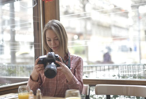 Young female photographer with photo camera sitting in cafe