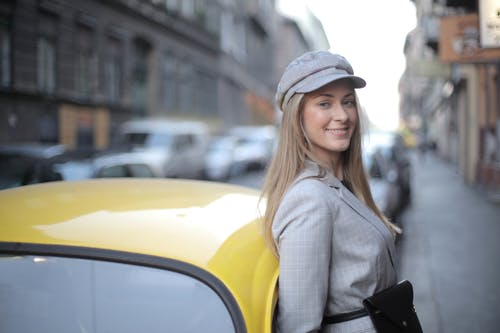Woman Wearing a Flat Cap Standing Beside Yellow Car