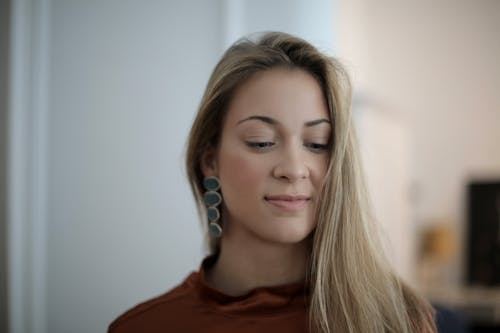 Smiling young woman in earrings at home