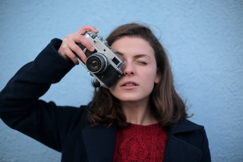 Woman in Black Blazer Holding Black and Silver Camera